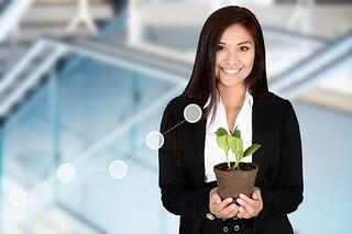 Photo of businesswoman nurturing a seedling