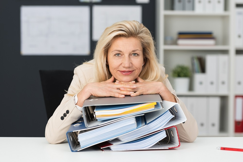 Photo of businesswoman with a stack of binders