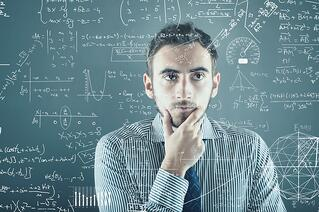 Photo of employee contemplating complex formulas